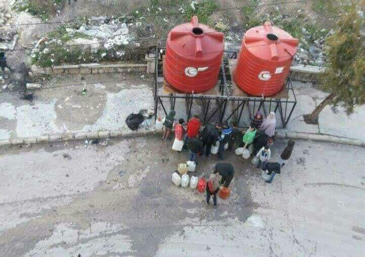 Residents of Aleppo gathering water at a water tank