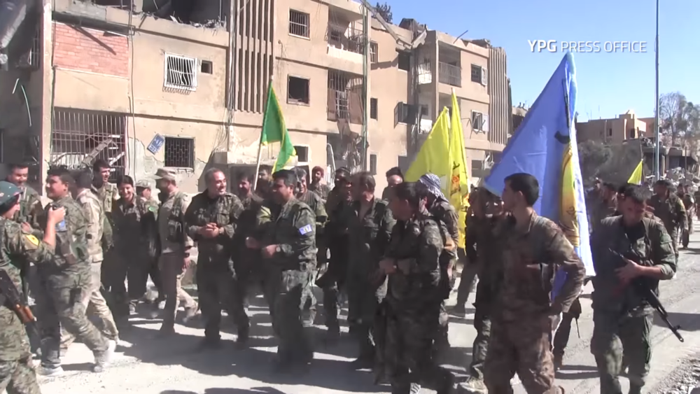 SDF fighters wave flags of their respective groups as they march through the final district of Raqqah taken from ISIS.