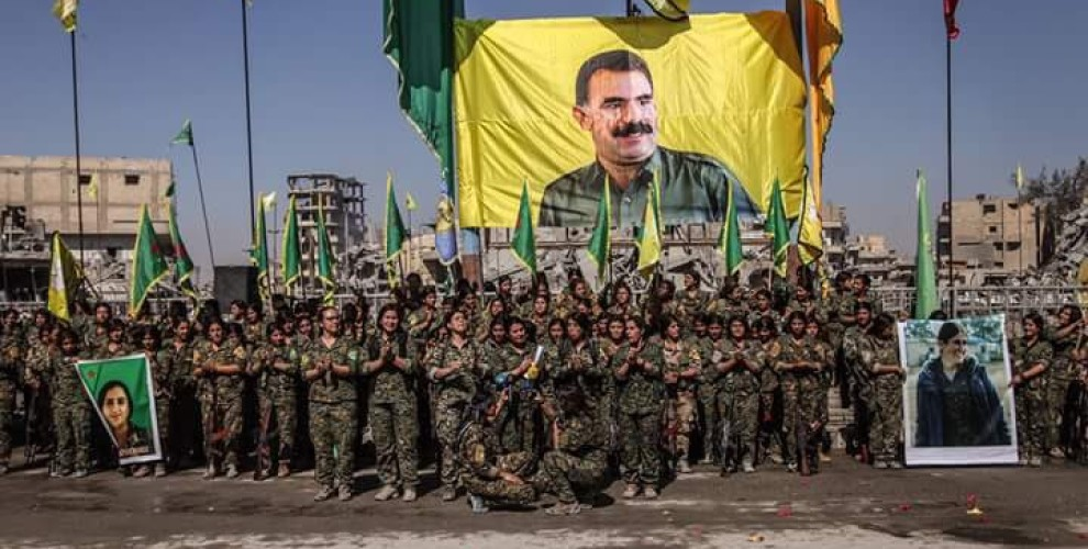 YPJ fighters stand in front of a giant portrait of PKK leader Abdullah Öcalan after the capture of Raqqah in October 2017. Turkey has used images like these to justify their ongoing border operation.