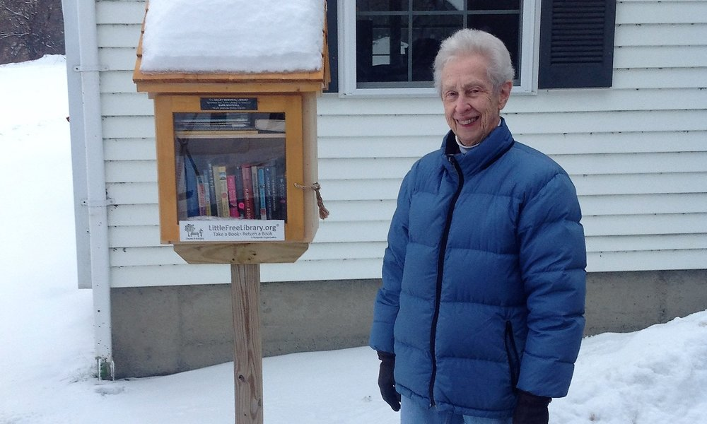 Former Librarian Extraordinaire and perennial volunteer Barbara Whitehill next to our little free library in morgan