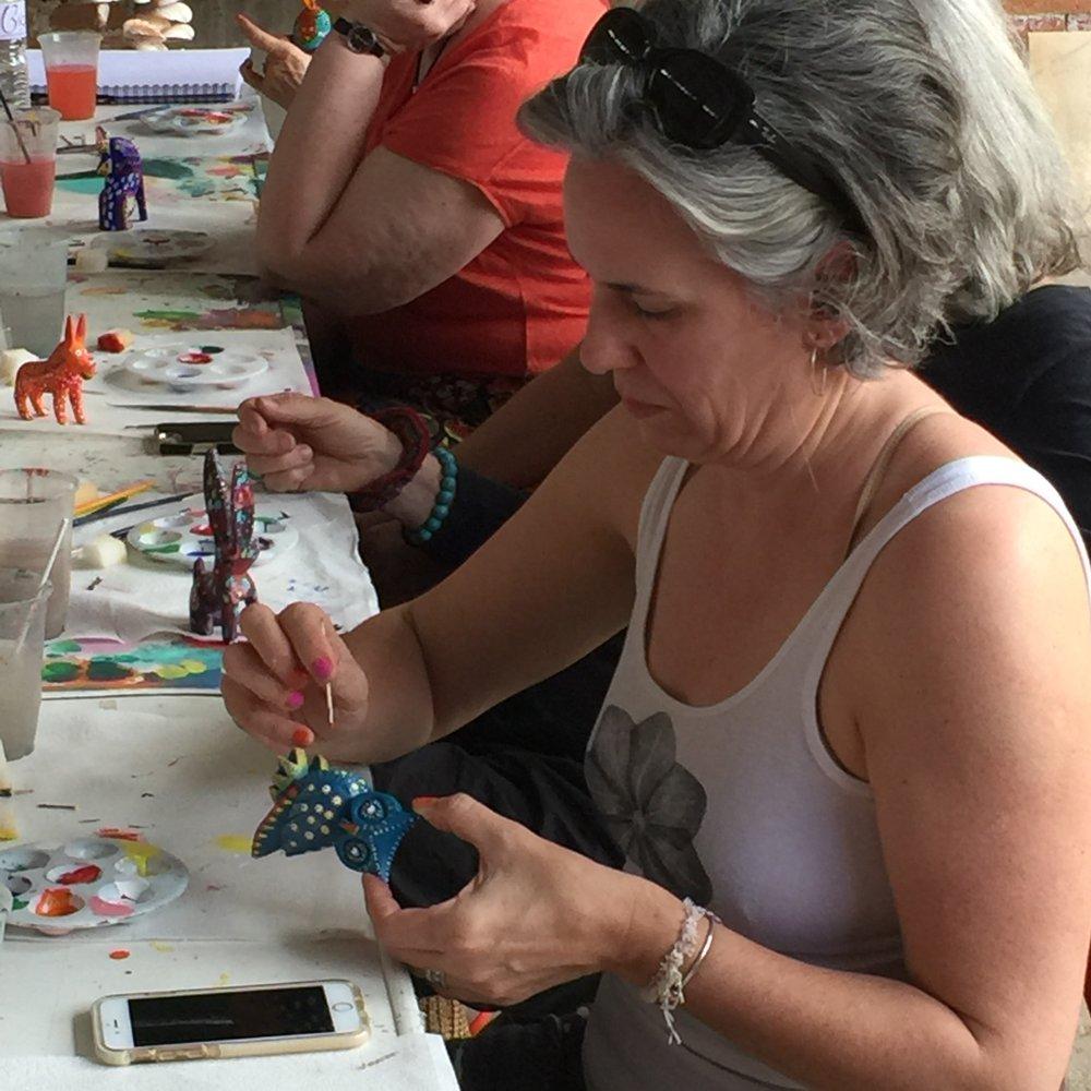 Cie painting her owl alebrijes