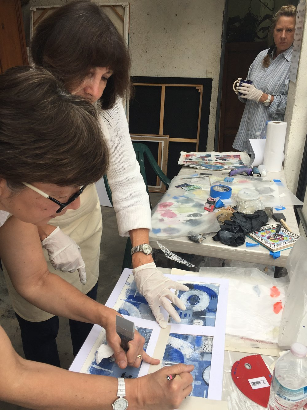 Pam shows Pilar how to use masking on her painting