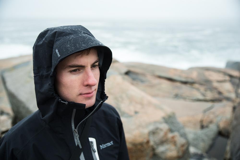 Man in rain on Nova Scotia coastline near Peggy's Cove
