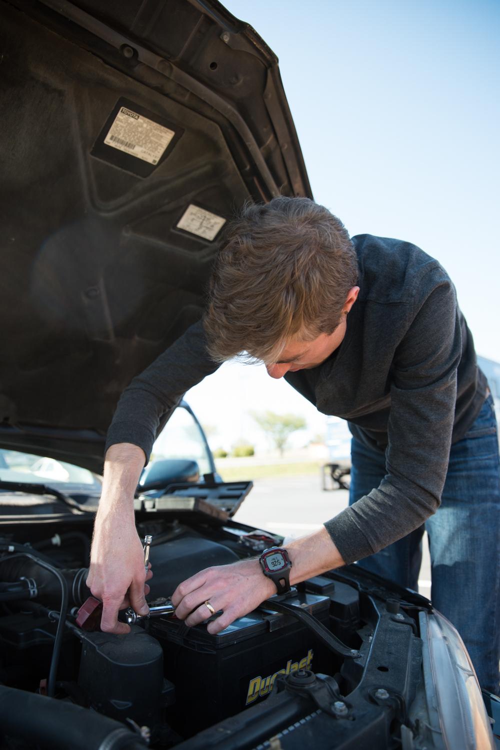 Man replaces dead battery in broken down car