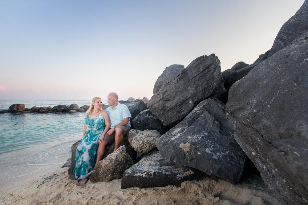 newly engaged couple sitting on rocks at Key West