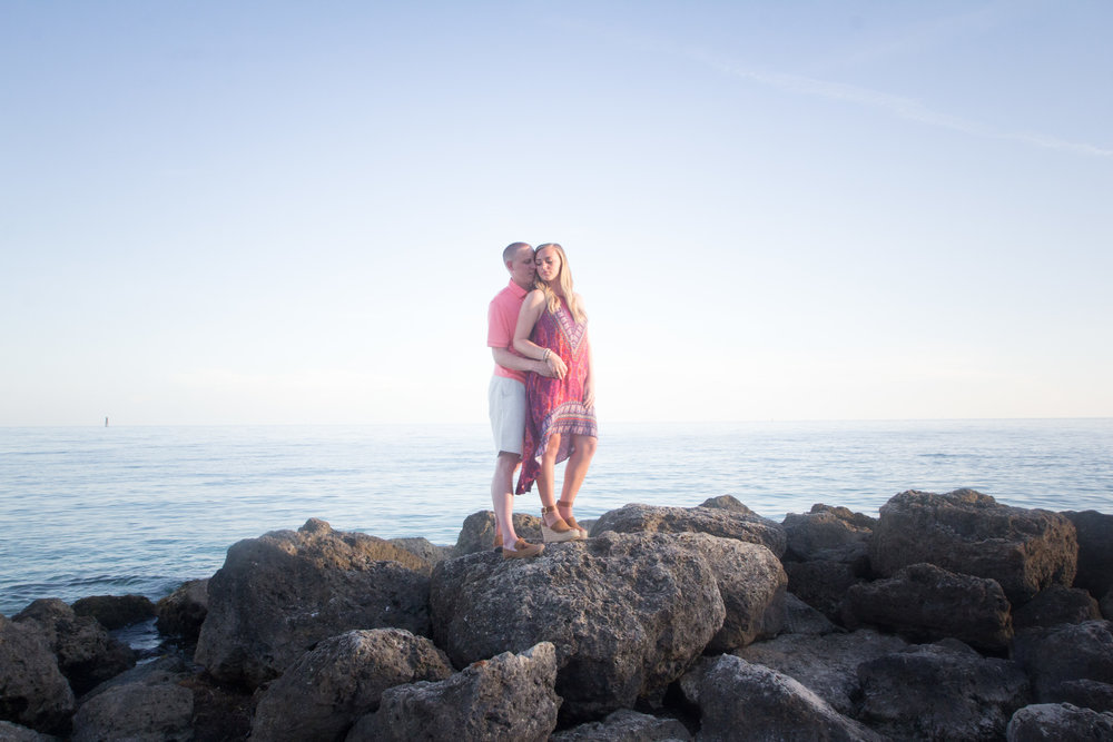 Newly engaged couple standing on rocks at Fort Zachary Taylor State Park Beach