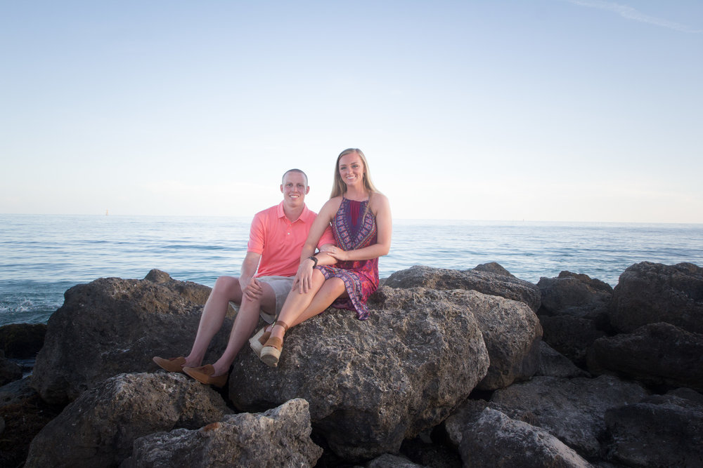 Newly engaged couple sit together on rock jetty