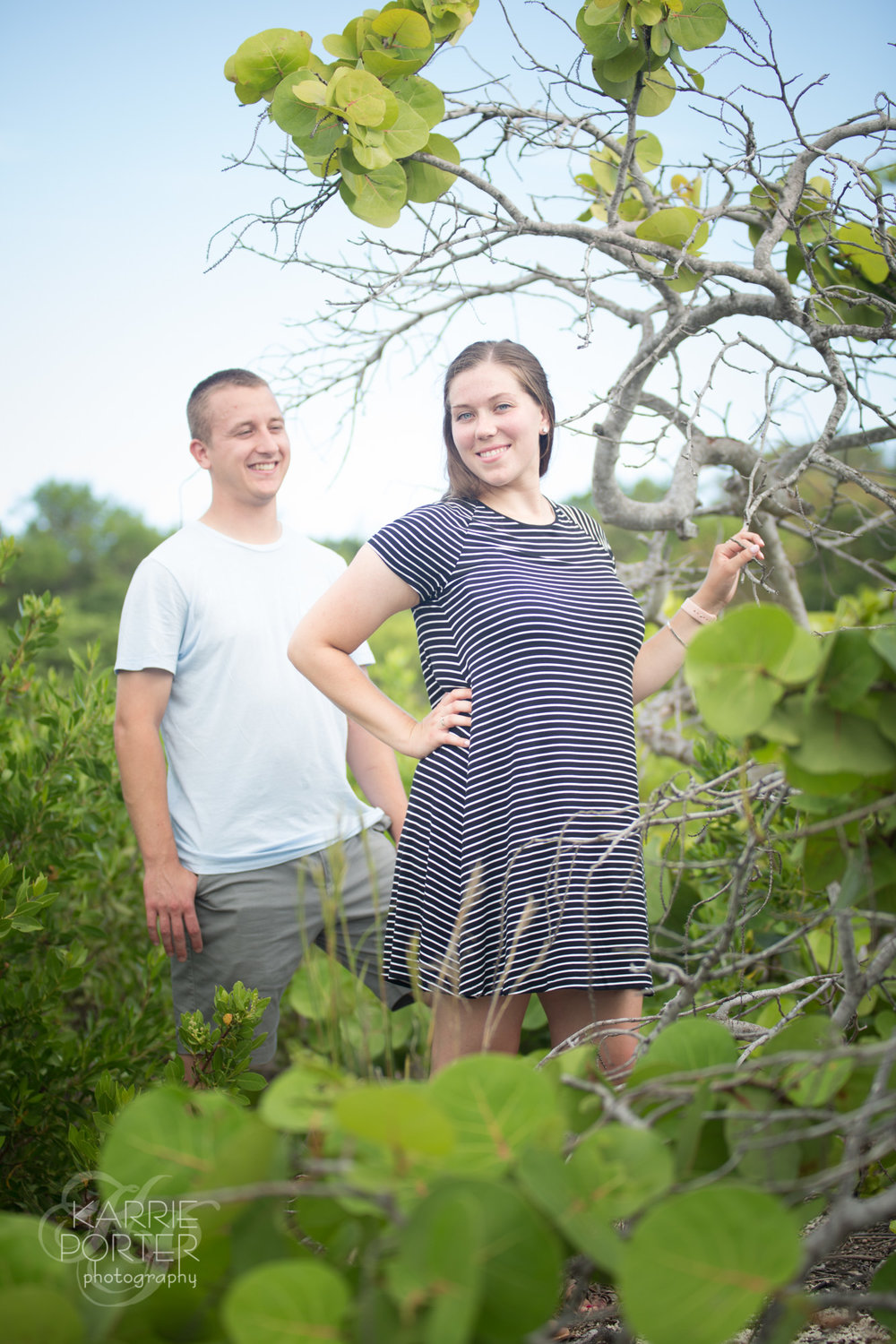 Engaged couple clamber through the tall brush to get a unique perspective of Key West foliage in their Proposal session photos
