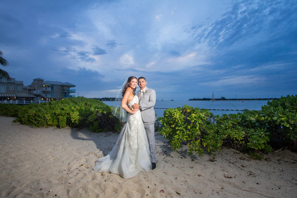 Bride and groom pose for the camera on the beach at Pier House Resort while the deep blue skies of Key West make a stunning background as the sun sets over the harbour.