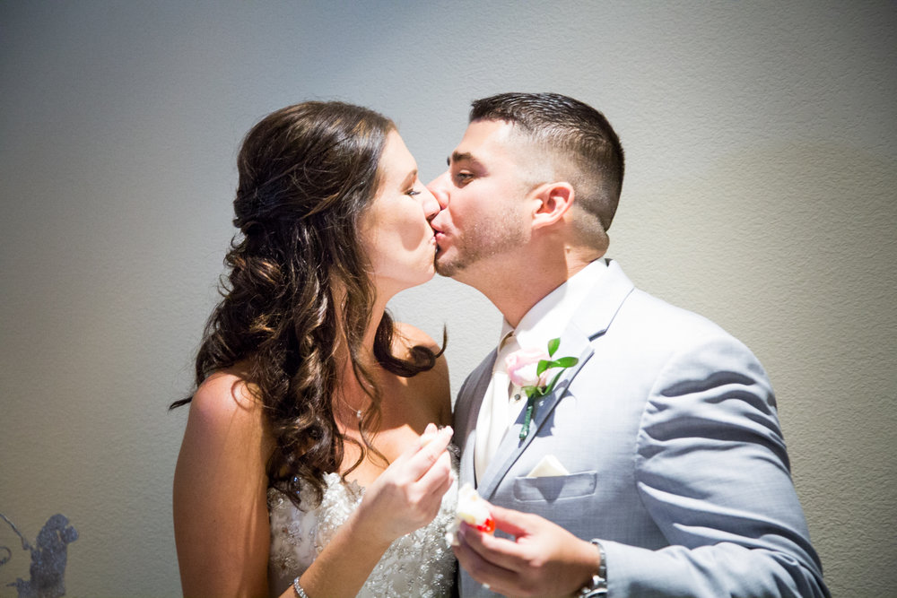 As the couple eats their wedding cake, guests cheered for one kiss.