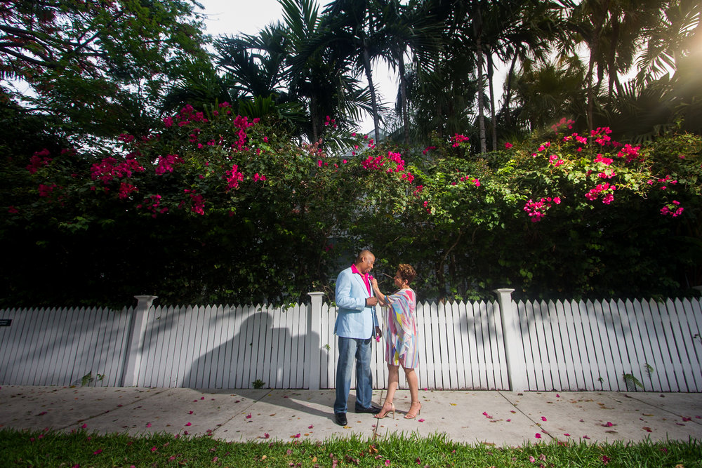 Engaged couple under pink flowers