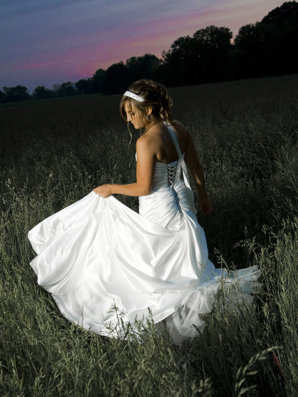 Bride-Holding-Dress-With-Pink-Sky-Behind-Her.jpg