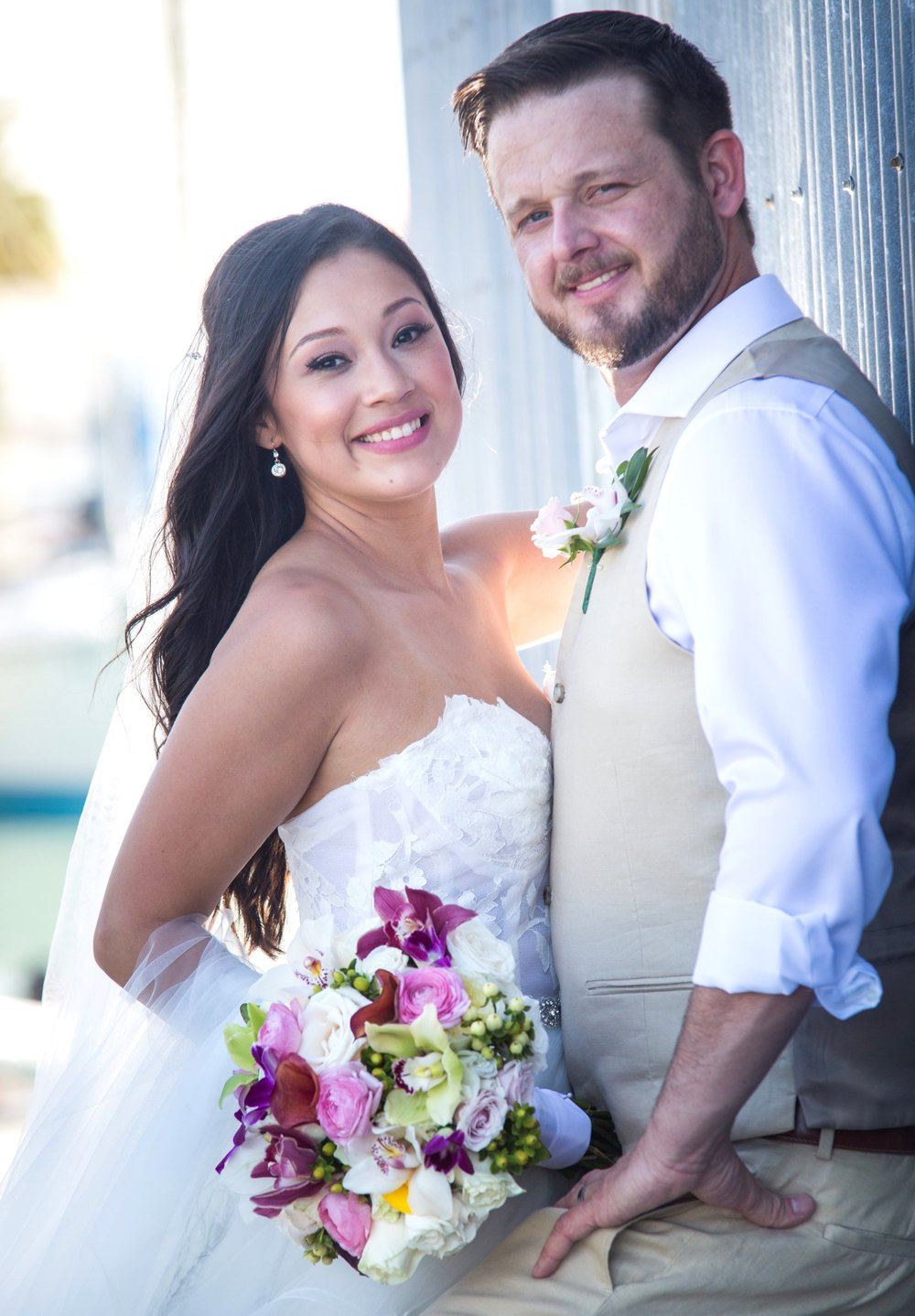 Couple pose next to Turtle History Museum in Key West Bight on wedding day