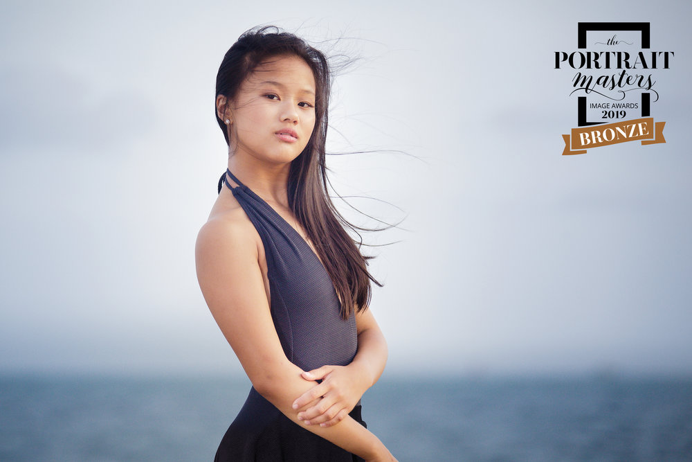 Portrait of a young woman posing on the rock jetty at Fort Zachary Taylor State Park in Key West Florida, winning Bronze Merit in the Portrait Masters international accreditation competition.