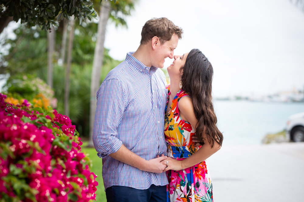 Couple giggling at each other with pink flowers on Sunset Key