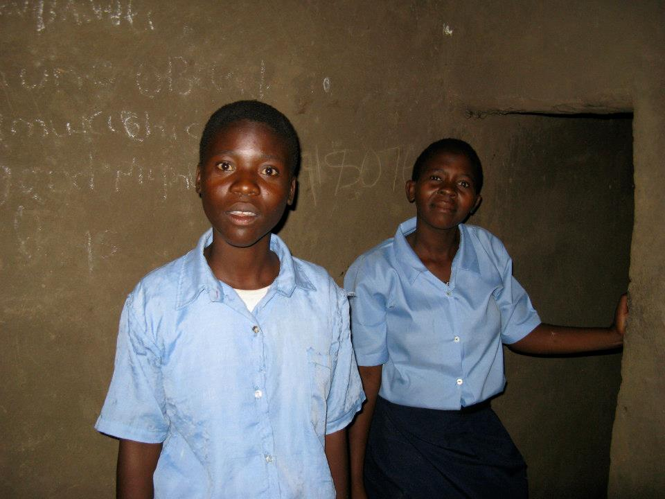 Two female students are somewhat surprised by the flash of a camera, as they show their home.