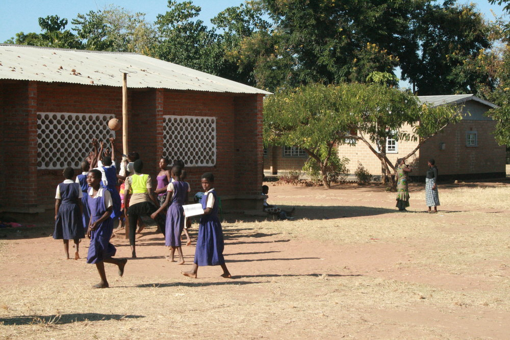 Primary school girls playing netball with a simple hoop.