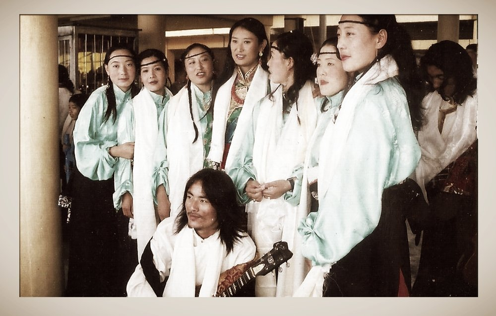 After graduating from TTS, I joined the Akupema group which was a Tibetan performing arts group which toured the whole of India. Whilst in Akupema I performed as a singer, dancer and musician. Performing with Akupema, I became more and more skilled at my instruments. However, Akupema didn't last long. Due to poor management of the group, members began to leave until I was the only one left and the group ceased to exist. And so I applied to the Norbulingka Institute as a modern artist. I worked as a modern artist, relief painter and music teacher. While living there I opened a hairdressing salon. This was the first modern hairdressing salon opened by a Tibetan. It was also whilst I was at Norbulingka that I opened my first tattoo shop. The skills required to be a relief painter – being able to paint a long line steadily, for example – are similar to those required for tattooing so these two skills went well together. I had actually started tattooing whilst I was part of the Akupema group. A friend in the group had created a tattoo on my arm painstakingly using a needle, and I had had the idea that it would be much better if there could be a machine to create the tattoo. So, I began working on a machine. The machine I eventually made comprised pieces from a cassette tape and ballpoint pen, and the battery pack from a keyboard and needles which I could change. And a lot of electrical tape. I began tattooing on the side using this home-made machine whilst I was at Norbulingka. I worked at Norbulingka for 2 and a half years. By the time I left, I had risen to be the main music teacher there, and I performed with my students at the 2006 Kalachakra held at Amaravati for His Holiness the Dalai Lama. After this performance I left Norbulingka and came to McLeod Ganj. It was July. For a while I didn't make tattoos but with the help of a friend from the USA, Serena, I bought professional equipment and opened a shop. In the beginning I didn't know how to use the modern tattooing equipment Serena had helped me buy. And so I had to learn. I learnt from Philip, a tattooist from Chicago (USA) who visited Dharamsala, and also from Claudia Fanti, another tattooist from Brazil. It was at this time that I also bought my first computer – for 3000 rs! I'd never used a computer before. After some time, I had made enough money by designing and selling T-shirts to invest in more expensive and better quality tattooing equipment, which is what I use today. (Today, vice versa is true – the tattoo money allows me to make better designed and better quality T-shirts!) My tattooing business is now very popular, and I am well-known as a tattooist-activist. I use my tattoos to make political statements about the Tibetan situation. Through my tattoos I have met people from all over the world. My work was recently featured in the London-based magazine Total Tattoo (May 2012 issue) and the German magazine Tätowier (March 2012 issue). I've also featured in the New York magazine Ink.