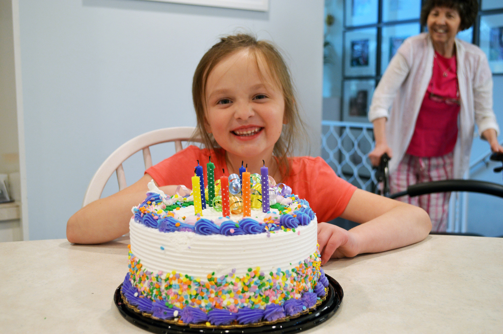 Abbey with her birthday cake. Grandma photo-bombing.