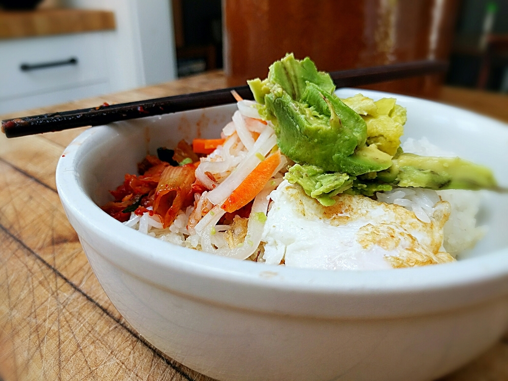 steamed white jasmine rice piled high with probiotic-rich homemade kimchi, pickled carrot and daikon, a fresh egg from our happy chickens and an avocado from our friends Ray and Barbara's tree.