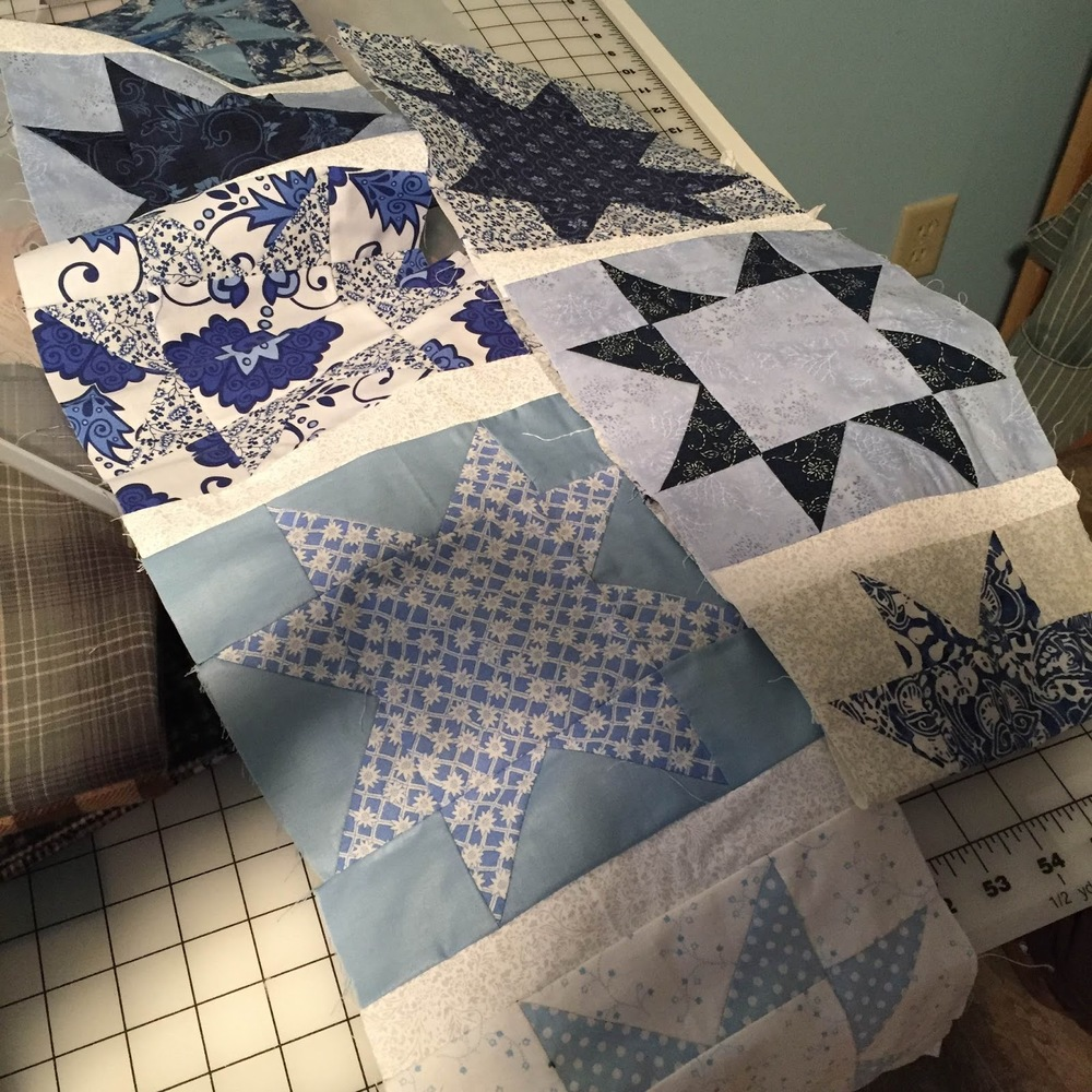 Sewing together the squares for a blue and white quilt.