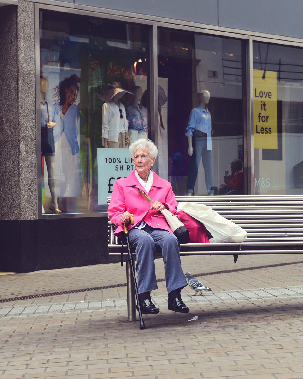 An elderly woman sits on a bench localted on New Kirkgate - Leeds main shopping strip.