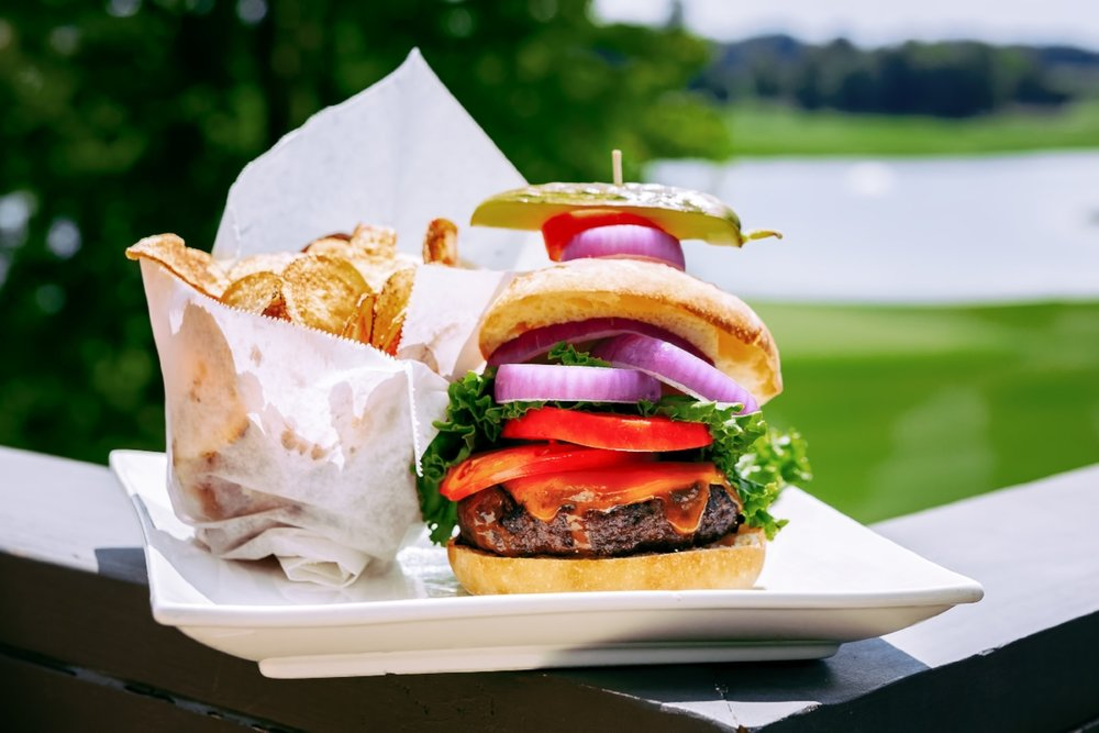 Food lifestyle shot of a hamburger overlooking the 18th hole at The Club at Longview.