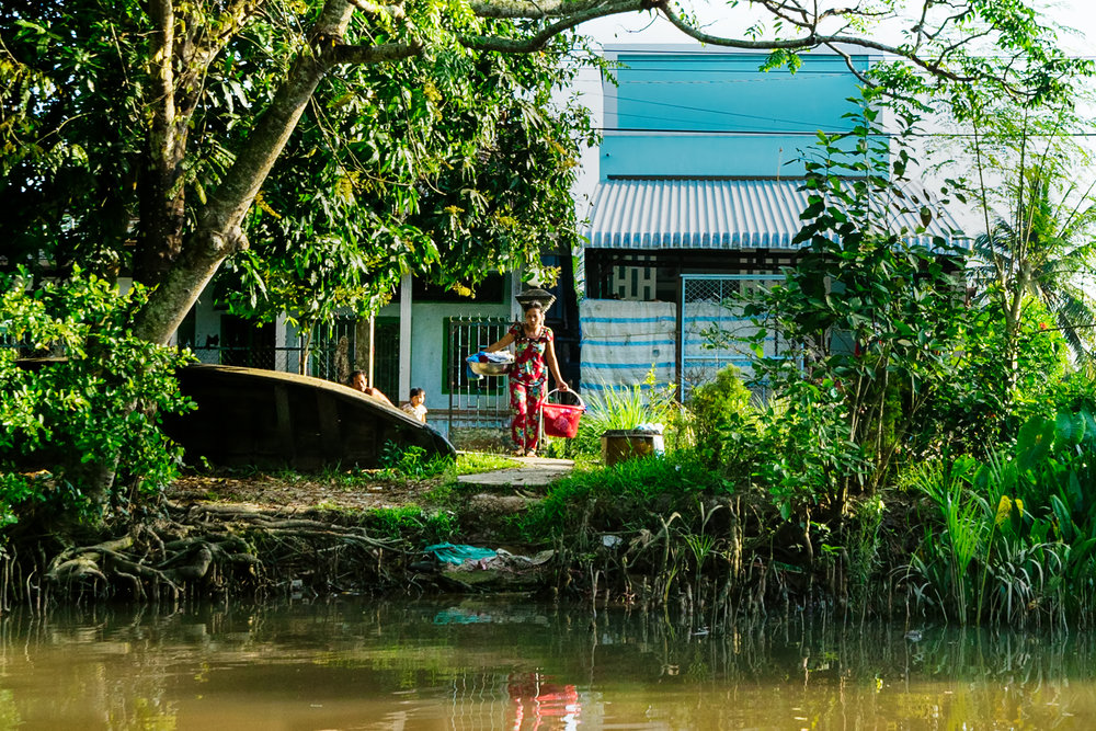 woman-walking-to-wash-clothes-on-Mekong.jpg