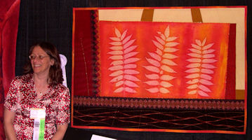 "November, 2007, posing with my prize-winning quilt, ""Sumac"", at the International Quilt Festival in Houston, TX.   Photo courtesy of Carolyn Sower."
