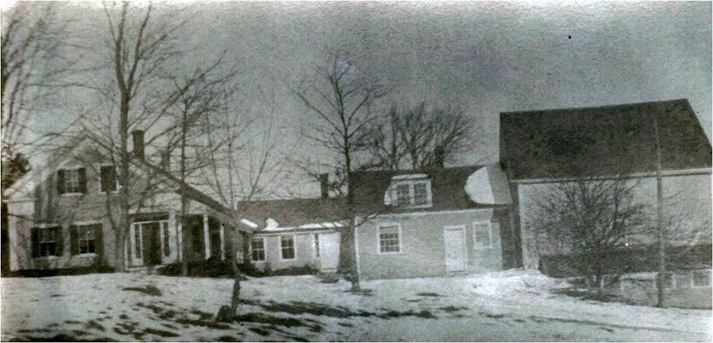 Historic images show that this Greek Revival house in East Grafton once had an earlier cape (background), ell, and barn.