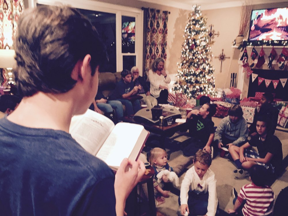 TJ reading the Christmas story as the kids wait to dive into presents. It was too hot for a real fire. So, we streamed one from YouTube.