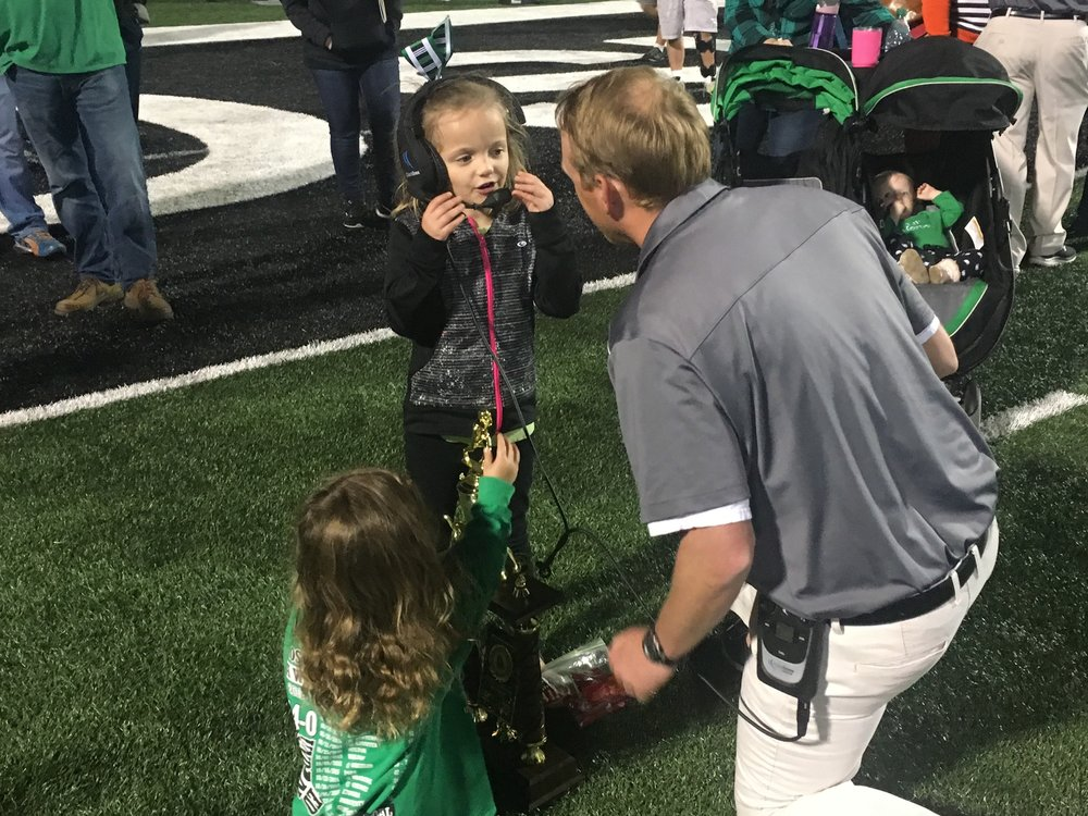 Coach Ford taking time with his daughters after a Roswell win.