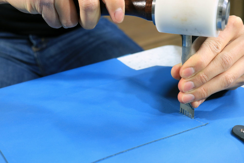 Tooling the leather tote bag with a diamond chisel and mallet
