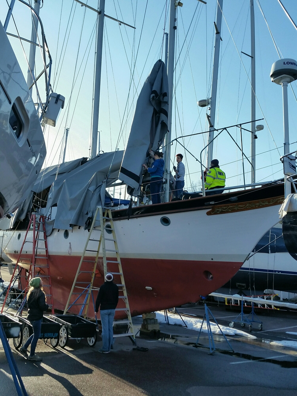 Sea Scouts removing the forward section of the winter cover.