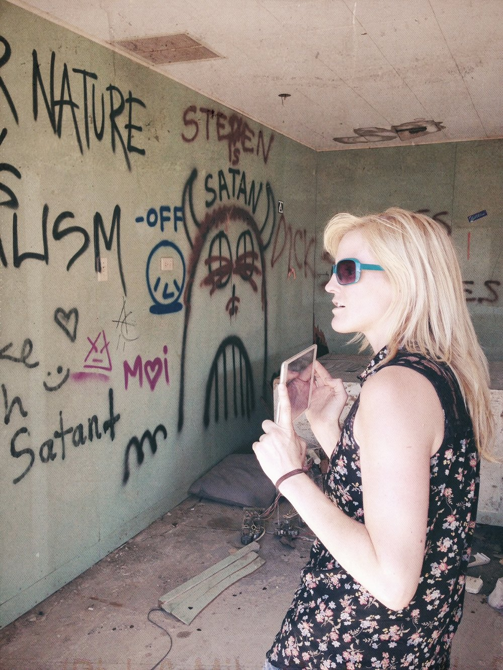 Diana explores the graffiti covered walls of an abandoned Bombay Beach dwelling