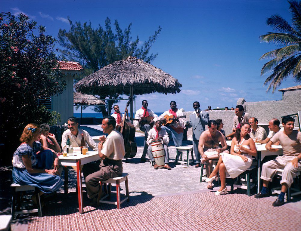 1946 Guests sit at outdoor tables in the Kastillito Club and talk together while a band performs in Varadero, Cuba.