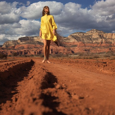 Model walking down a red dirt road in the Arizona desert - Vogue Magazine 1968