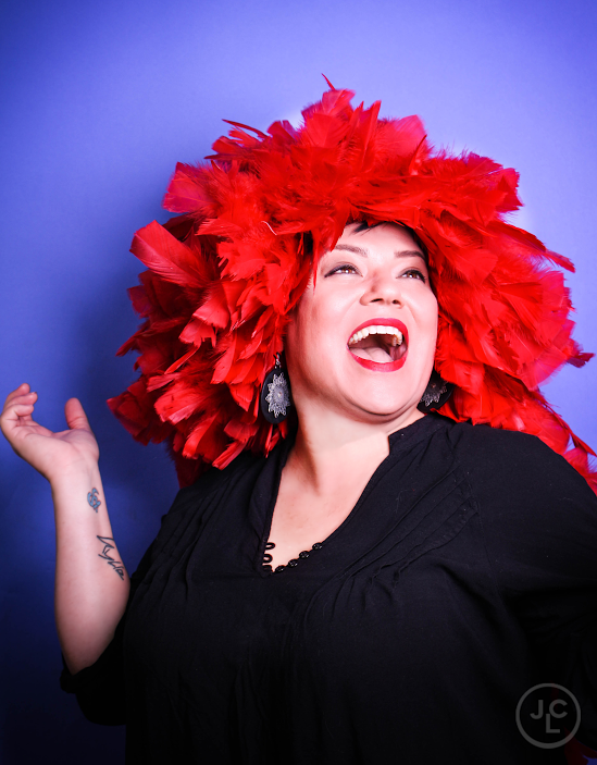 """Dina Nina Martinez, who was called """"very funny"""" by The Late Late Show's James Corden, is a transgender standup comedian and actor from LA who currently resides in Chicago. Her signature blend of disarming sass and charm has been featured in comedy festivals and multiple world-class comedy venues including LA Pride, The Chicago Women's Funny Festival, LA's The Comedy Store, and Chicago's Zanies Comedy Club. She is a Huff Post blogger and creator and executive producer of Lady Laughs Comedy Festival.She was named one of the """"40 Hot Queer Women In Comedy"""" by AfterEllen.comand won Madison's Favorite Local Comedianas voted by the readers of the Isthmus. Though LA was cute and she's certainly got fabulousness to spare, Martinez's long term goals are to settle down and be a soccer mom."""