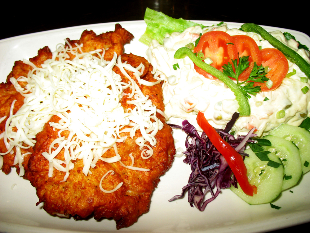 Pork schnitzel in potato pancake batter-topped with cheese with potato salad