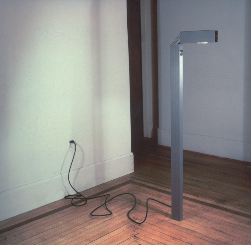 As minimal reaction to post-modern excess, a simple structural steel tube is used to create a floor lamp. The top of the lamp hinges, thus allowing for two directional lighting. In the standard position, the lamp produces ambient uplighting. In the hinged position, a reading light is produced. The lamp utilizes halogen fixtures – new for the time. The bottom of the lamp is integral to the floor and contains no base. Exploring the integrity of a material allows for a fusion of form and function – one relating to the other, not one apriori to the other.