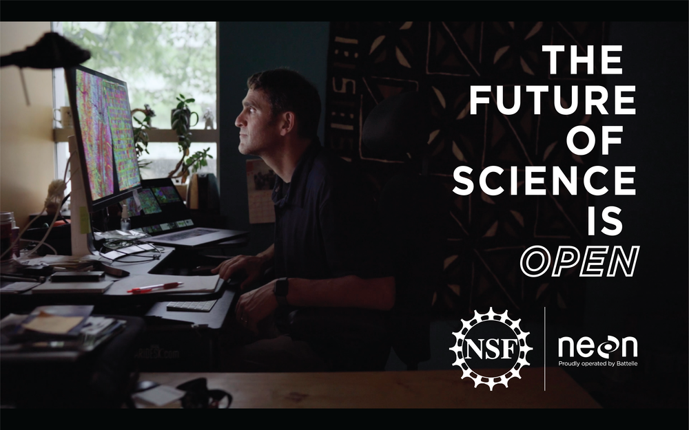 Promotional photo for the Future of Science Is Open film. Features a man sitting at his computer, with the light from the screen illuminating his face. He is looking at an image of spectral data.