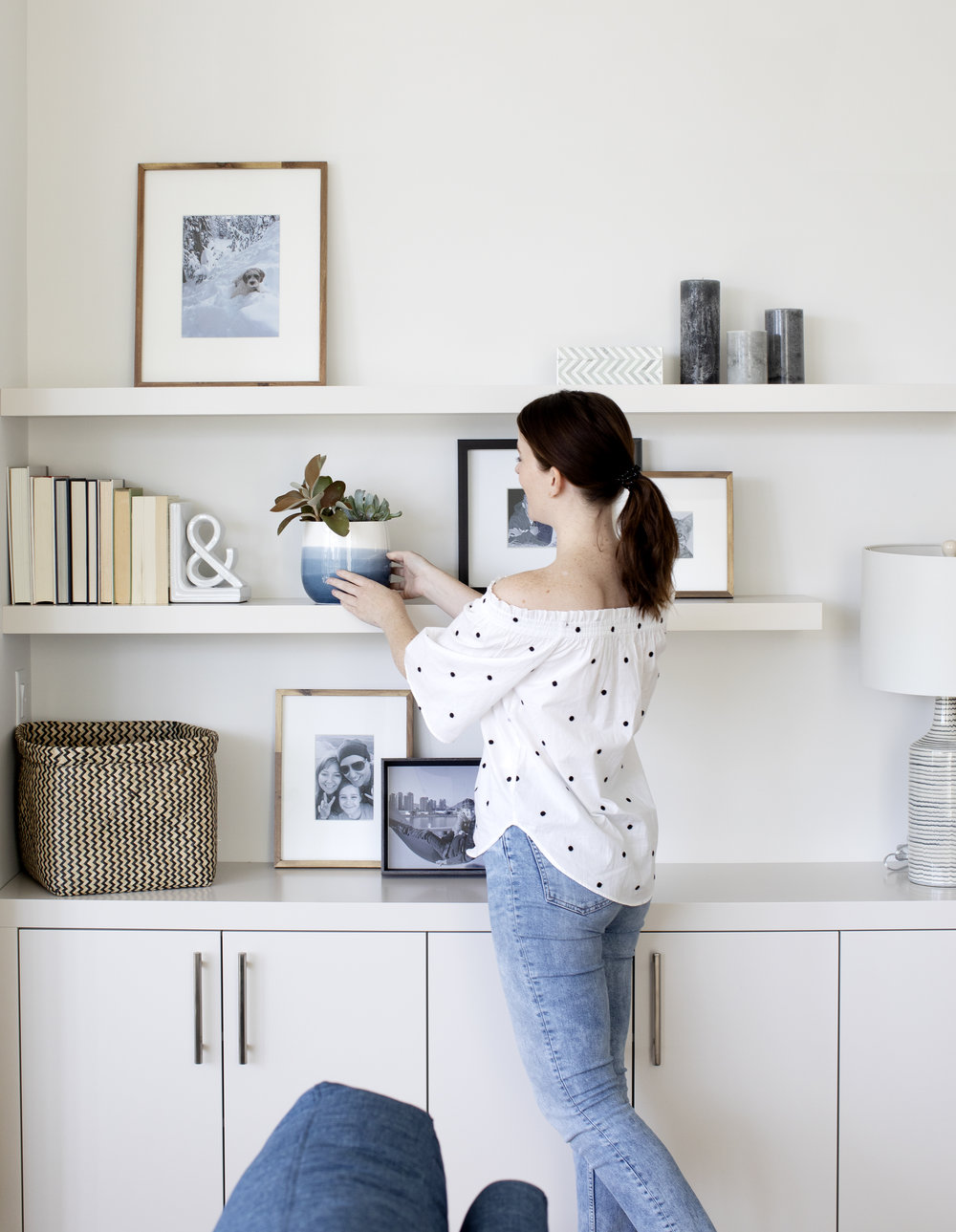 Framed family photos and loved items on the shelf. Decor thought through down to the last detail makes the space feel like home.