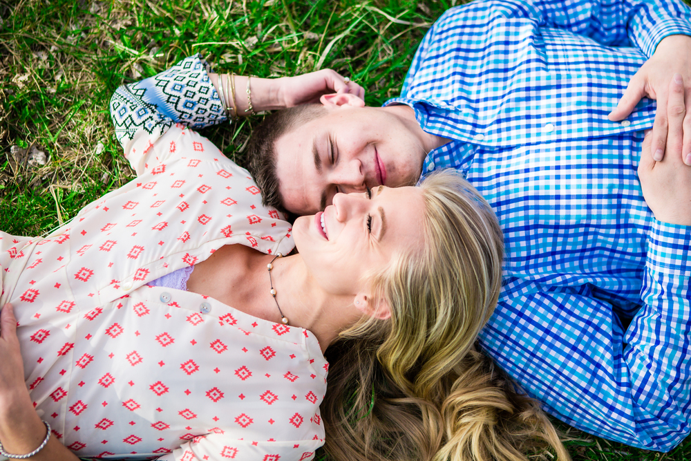Couple laying in the grass. Engagement taken at Lions Park in Fort Collins Colorado by Jared M. Gant