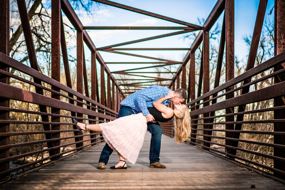 Engagement pictures of couple dipping taken on Lion Park bridge in Fort Collins Colorado by JMGant Photography