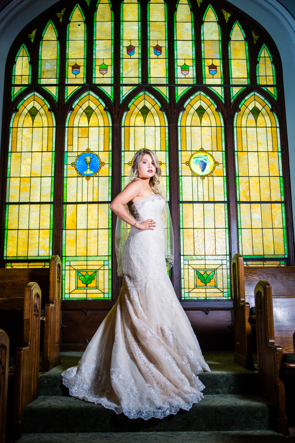 Bride in front of stain glass window. www.jmgantphotography.com