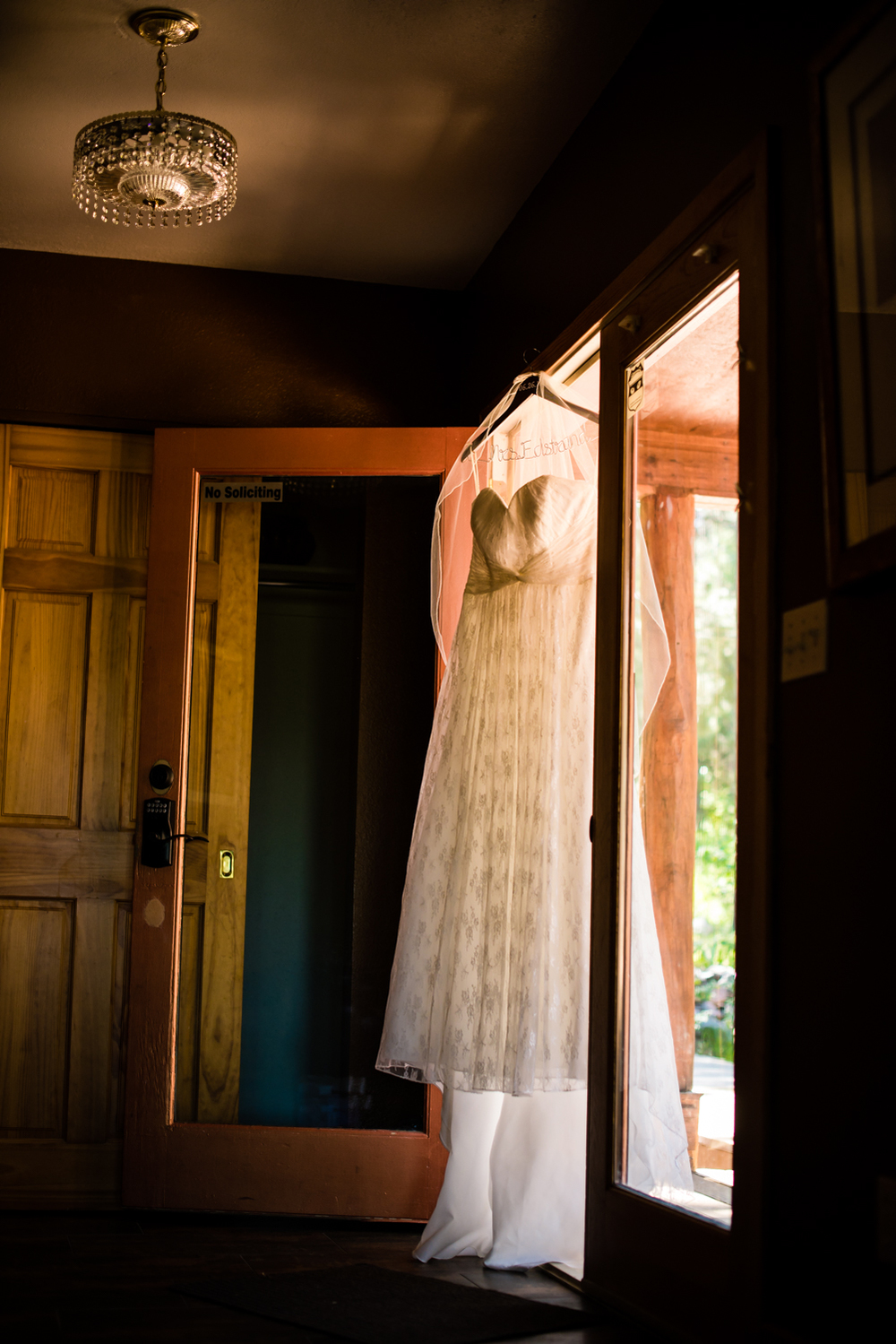 Wedding dress hanging in doorway for  a Deer Creek Valley Ranch Wedding. Photographed by JMGant Photography.