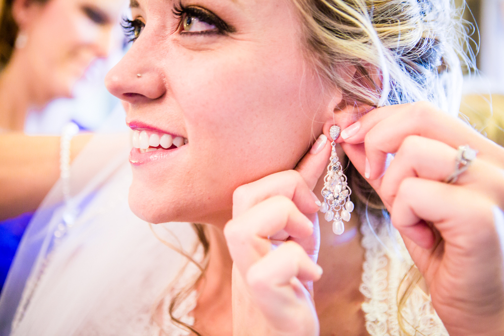 Bride putting her earrings in.The barn at Evergreen Memorial. Photographed by JMGant Photography.