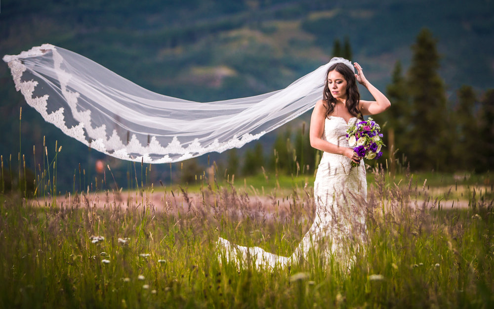 The bride's veil blowing in the wind.Vail Colorado Wedding photographed by JMGant Photography.