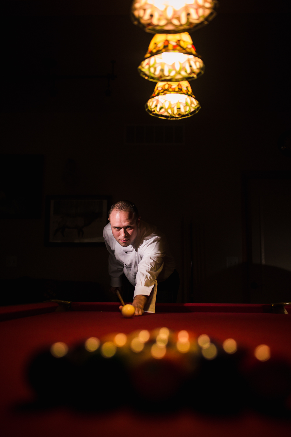 Groom playing pool by JMGant Photography.