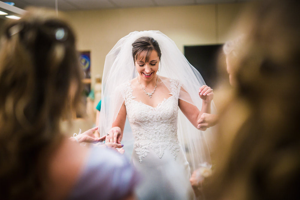 Helping the bride get ready  by JMGant Photography.